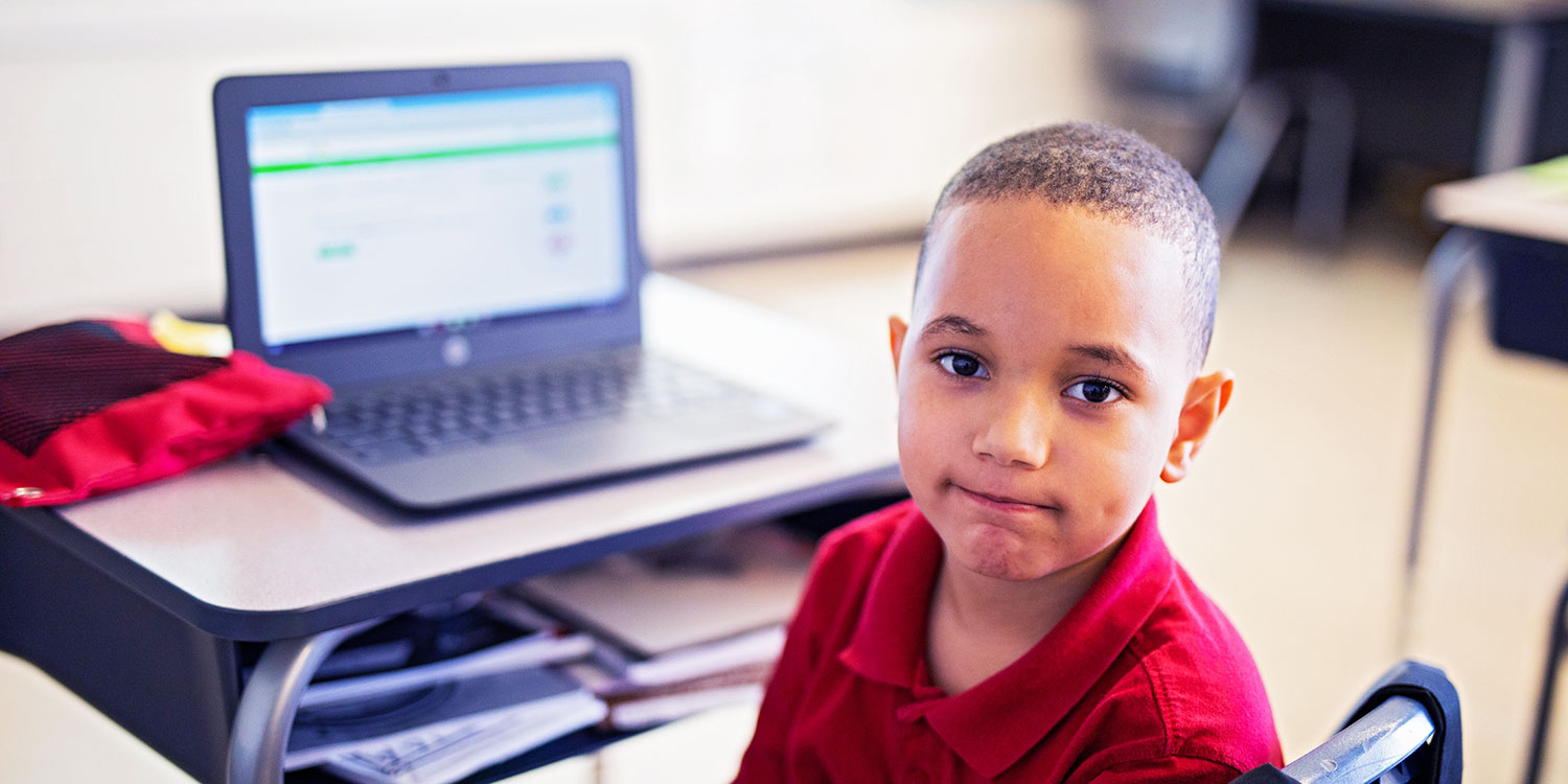 Elementary student working on laptop at their desk.