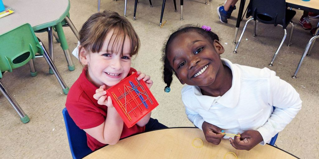 Smiling elementary students showing an activity in a classroom.